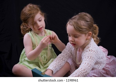 Little girls examining contents of an antique jewelry box