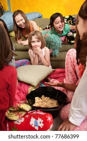 Little girls giggle and eat snacks at a sleepover