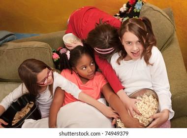 Little girls grab popcorn at a sleepover