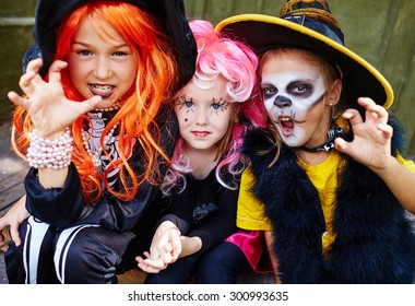 Little girls in Halloween costumes looking at camera with frightening expression