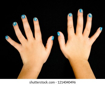 Little girls hands with blue manicure decorated with flowers against black
