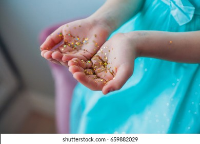 Little girls hands covered with gold glittering stars