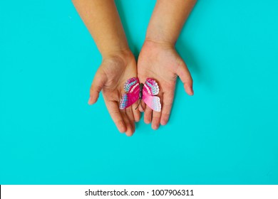 Little girls hands holding butterfly, on blue background