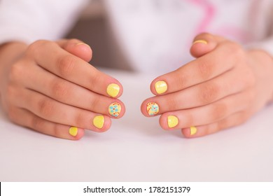 Little girl's hands with yellow nails. Beautiful and safety manicure for children.