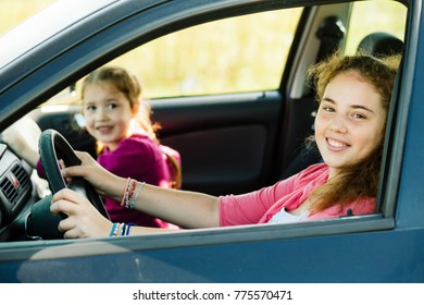Little girls having fun in the family's car and looking to the camera.