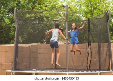 Little girls having fun jumping and playing on a trampoline.