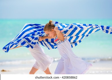 Little girls having fun running with towels on tropical beach with white sand and turquoise ocean water