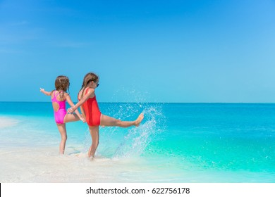Little girls having fun at tropical beach playing together at shallow water