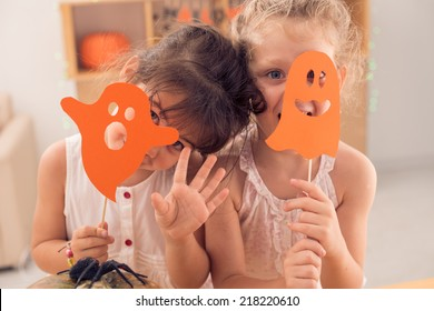 Little girls hiding faces behind paper ghosts
