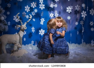 little girls hugging each other on christmas decorated background