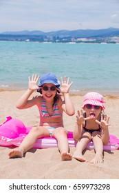 little girls  lying on  sandy beach and sunbathe in the sun