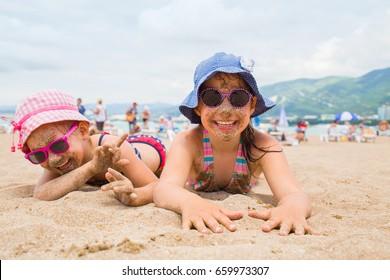 little girls  lying on a sandy beach and sunbathe in the sun