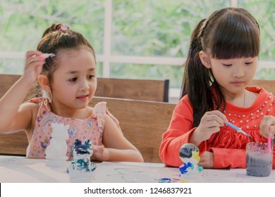 Little girls painting ceramic model in classroom or painting together at the school or kindergarten. Concept for art and creative education. Kids hobby.