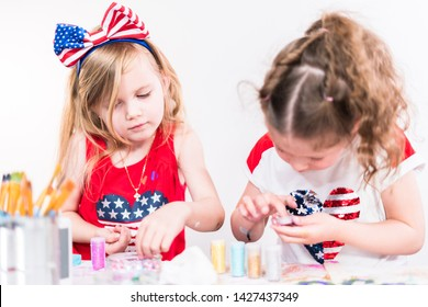 Little girls are painting on canvas on July 4th party.