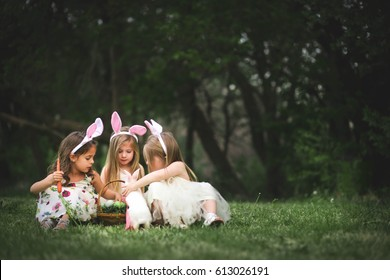 Little girls play with Easter bunny and Easter Basket