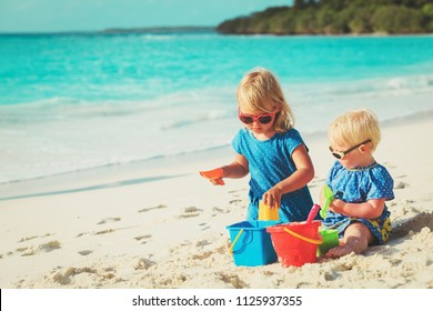 little girls play with sand on beach