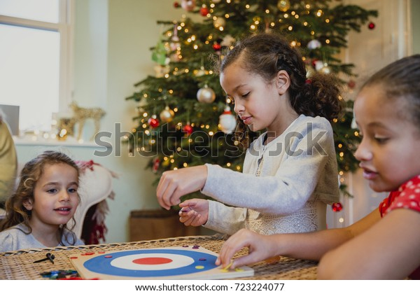 Little girls are playing board games in their home at christmas time.