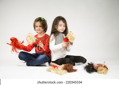 Little girls playing with dolls with light grey background