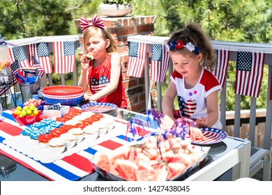Little girls are playing at the July 4th party on the back patio.