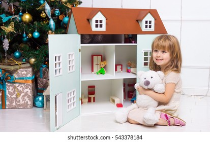 A little girls playing near the Christmas tree in the house for dolls with bear
