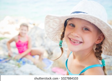 little girls playing on the beach and sunbathe in the sun