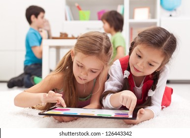 Little girls playing on a tablet computing device - laying on the floor