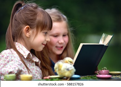 Little girls playing outdoors. They are reading the book and playing with chickens together