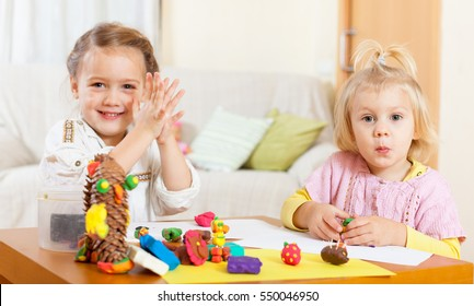 little girls playing with plasticine at house at  table.
