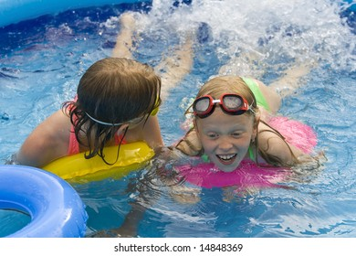 Little girls playing in th blue paddling pool