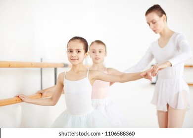 Little girls practicing dances at wooden machine with pedagogue in white class