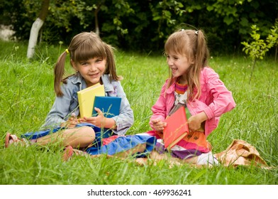 Little girls reading book on the lawn and tell each other something interesting
