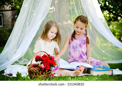 Little girls reading a book together in the park under the canopy