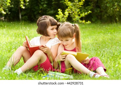 Little girls reading books on the lawn and tell each other something interesting