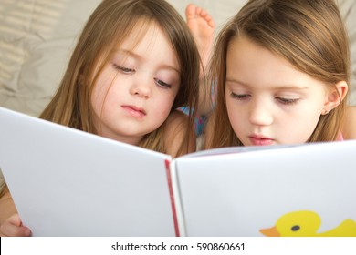 Little girls reading a story together