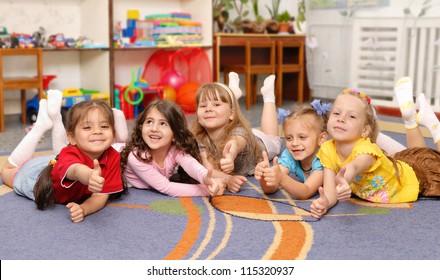 Little girls show sign OK. Kindergarten children