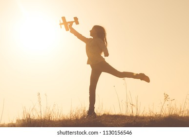 Little girl's silhouette holding small toy airplane. Cheerful girl standing on one leg on the meadow at sunset time