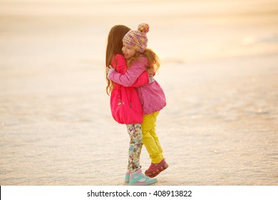 little girls sisters hugging and holding hands in nature. childr