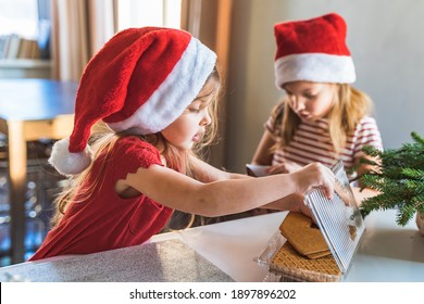 Little girls, sisters in red santa claus hats make christmas gingerbread house. Covered by white glaze, cream with walls, roof, windows, chimney. Decoration with bright multicolored sweets, lollipops.