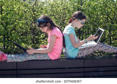 Little girls sitting with laptop in the park.
