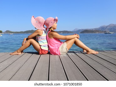 little girls sitting on the beach and sunbathe in the sun