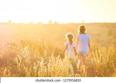 Little girls stand by holding hands looking on sunshine evening field