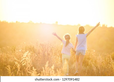 Little girls stand by holding hands looking on sunshine evening field with joyfully raised hands