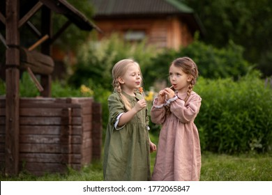 Little girls stand near a wooden well. Girls eat lollipops. A wooden house is visible from behind. Girls in dresses and pigtails. Image with selective focus.