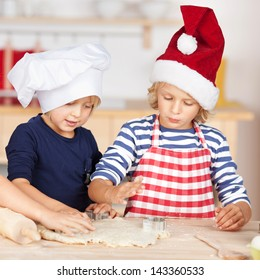 Little girls standing at a kitchen counter baking Christmas cookies cutting pastry with a cookie cutter