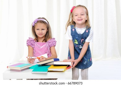 Little girls are studying literature. Reads a book while sitting at a white table.