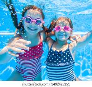 little girls swimming  in pool  underwater.