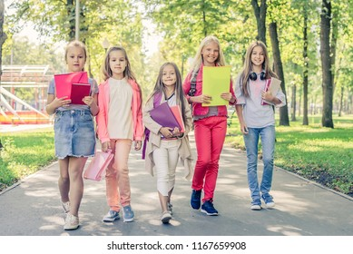 Little girls walking in the park with school books and notes