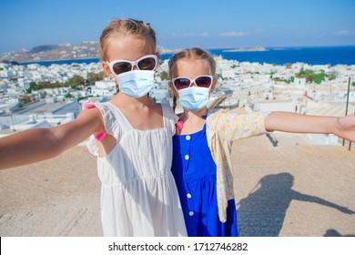 ヨーロッパ、ギリシャ、ギリシャ、ミコノス島の背景に、典型的なギリシャの伝統的な村で、ウイルス防止のためにマスクをした少女たち。