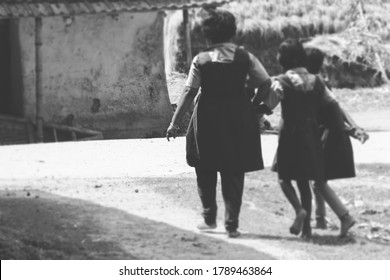 Little girls wearing uniform and playing on the road while got break for meal on a primary school. Happy cheerful childhood. Nostalgia. Practicing or playing Chu kit kit on the road. Sunny day. Bnw.