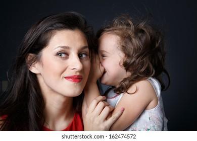 Little girls whispers secretly in mother ears